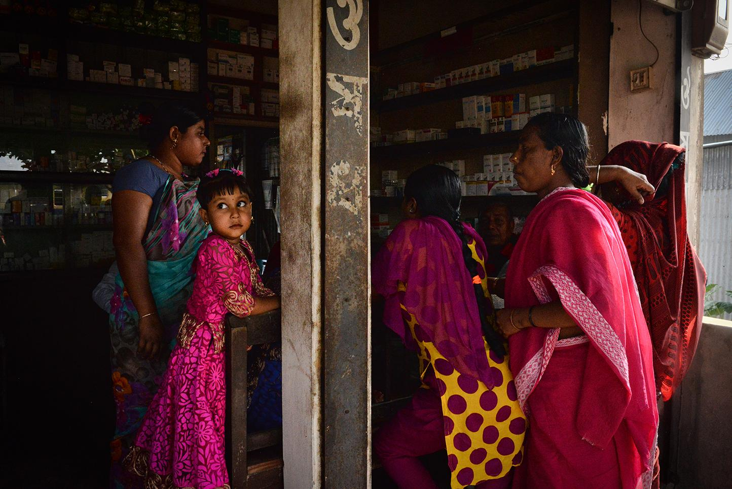 Women with their children buy steroids at a pharmacy just outside of Daulatadia Brothel in Daulatadia, Rajbari, Bangladesh. Steroids plump up the face, which some in Bangladesh find a round face to be a sign of beauty. Daulatadia is considered one of the largest brothels in the world and serves roughly 2500-3000 men daily. Bangladesh is the only Muslim country in the world where prostitution is legal. Though legally prostitutes must be at least 18 years of age many are tricked into the profession at a very young age.
