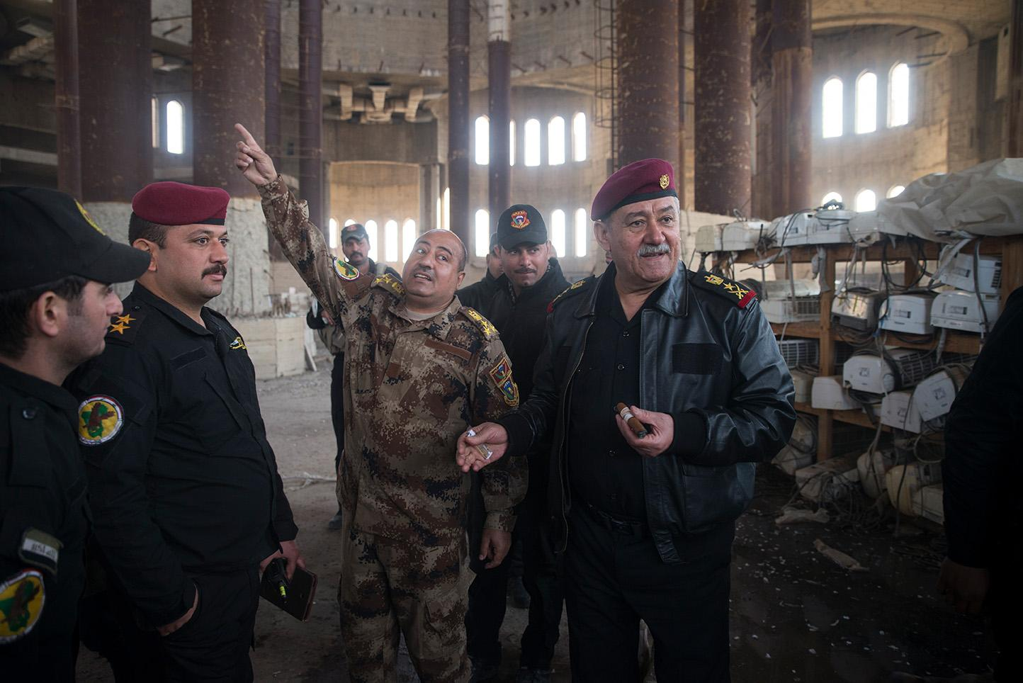 Mosul, Iraq. A member of Iraq Special Forces show Abdul-Ghani al-Assadi commander of Iraq's anti-terrorism unit the recently liberated Great Mosque of Mosul, a Sunni mosque originally built by Saddam Hussein, though construction was never completed. The mosque was used as a training school for Islamic State militants, a storehouse for stolen items and one area was turned into a prison for Mosul residents who did not obey ISIS rules. It also served as a stage for filmed beheadings by the Islamic militants. The Great Mosque was liberated on January 18th, 2017.