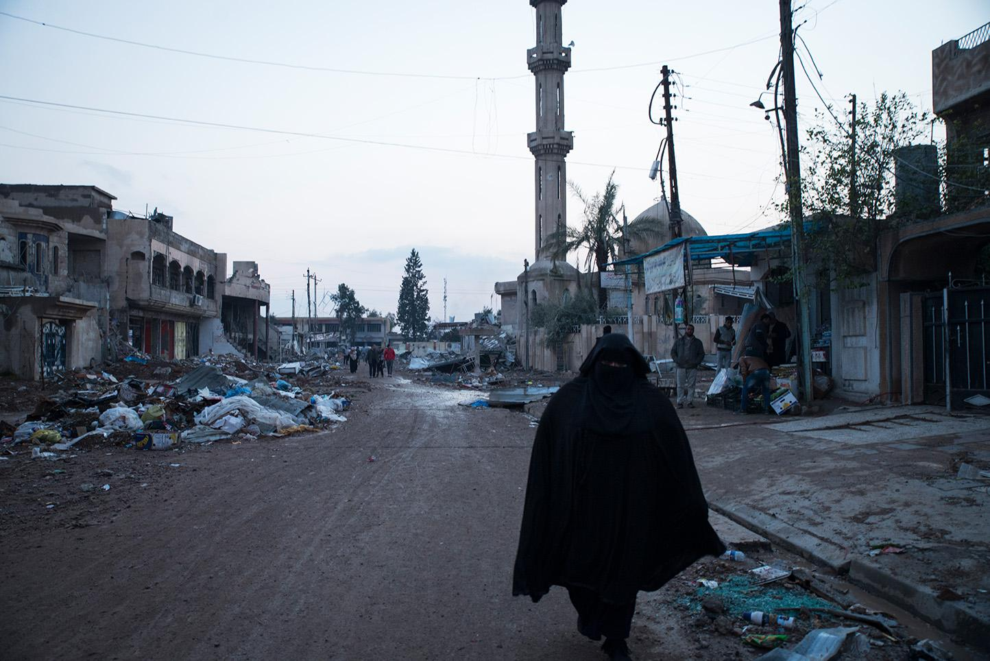 Mosul, Iraq. A woman walks past a mosque destroyed by ISIS in the Al Sukar neighborhood of eastern Mosul. For more than two and half years Mosul, Iraq's second largest city has been under the control of the Islamic State of Iraq and the Levant (Isil). Since October of 2016, Iraq Special Forces with the help of the American military implementing coalition airstrikes has begun the battle to take back Mosul.