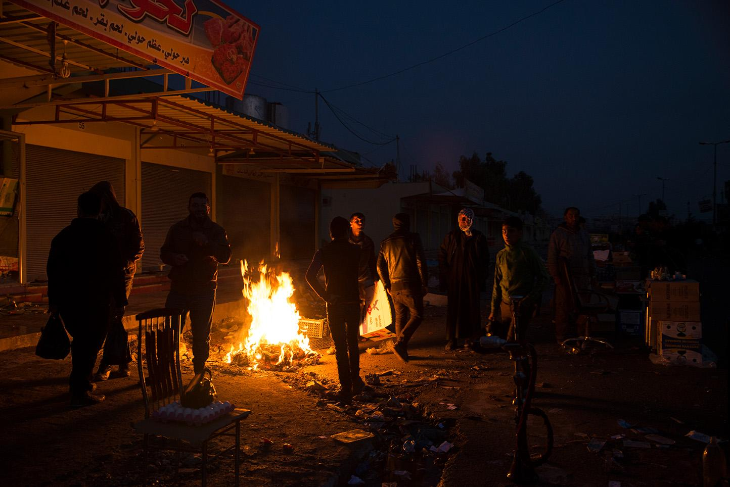 Men rest by a fire at the market in the recently liberated neighborhood of Al Sukar in eastern Mosul. ISIS has used drones with grenades to target busy areas where many civilians congregate. Though eastern Mosul is considered fully liberated by the Iraq Army, possible ISIS snipers, trip wires, and IEDs [improvised explosive devices] are still a threat to civilians. For more than two and half years Mosul, Iraq's second largest city has been under the control of the Islamic State of Iraq and the Levant (Isil). Since October of 2016, Iraq Special Forces have begun the battle to take back Mosul.