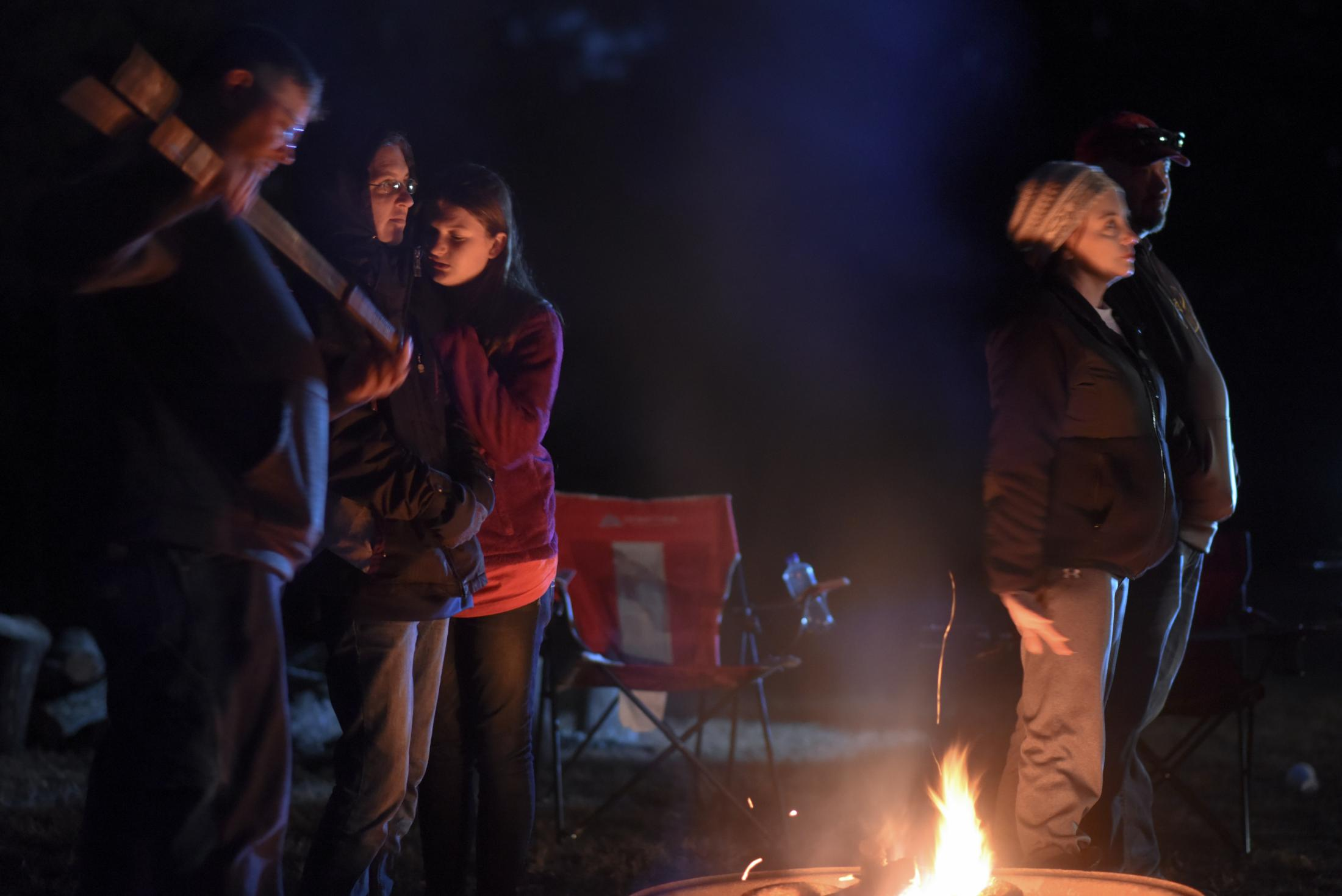 From left, Joey Kaup, Christy Popp, her daughter Shannon Popp who is on the Poplar Bluff trapshooting team and Angie Rideout stand around a campfire at the Poplar Bluff Gun Club in Poplar Bluff, Missouri on November 9, 2019. As of 2016, Missouri was the top Midwest state, and seventh in the nation, in the amount of NRA Foundation money given to schools and 4-H groups this decade.