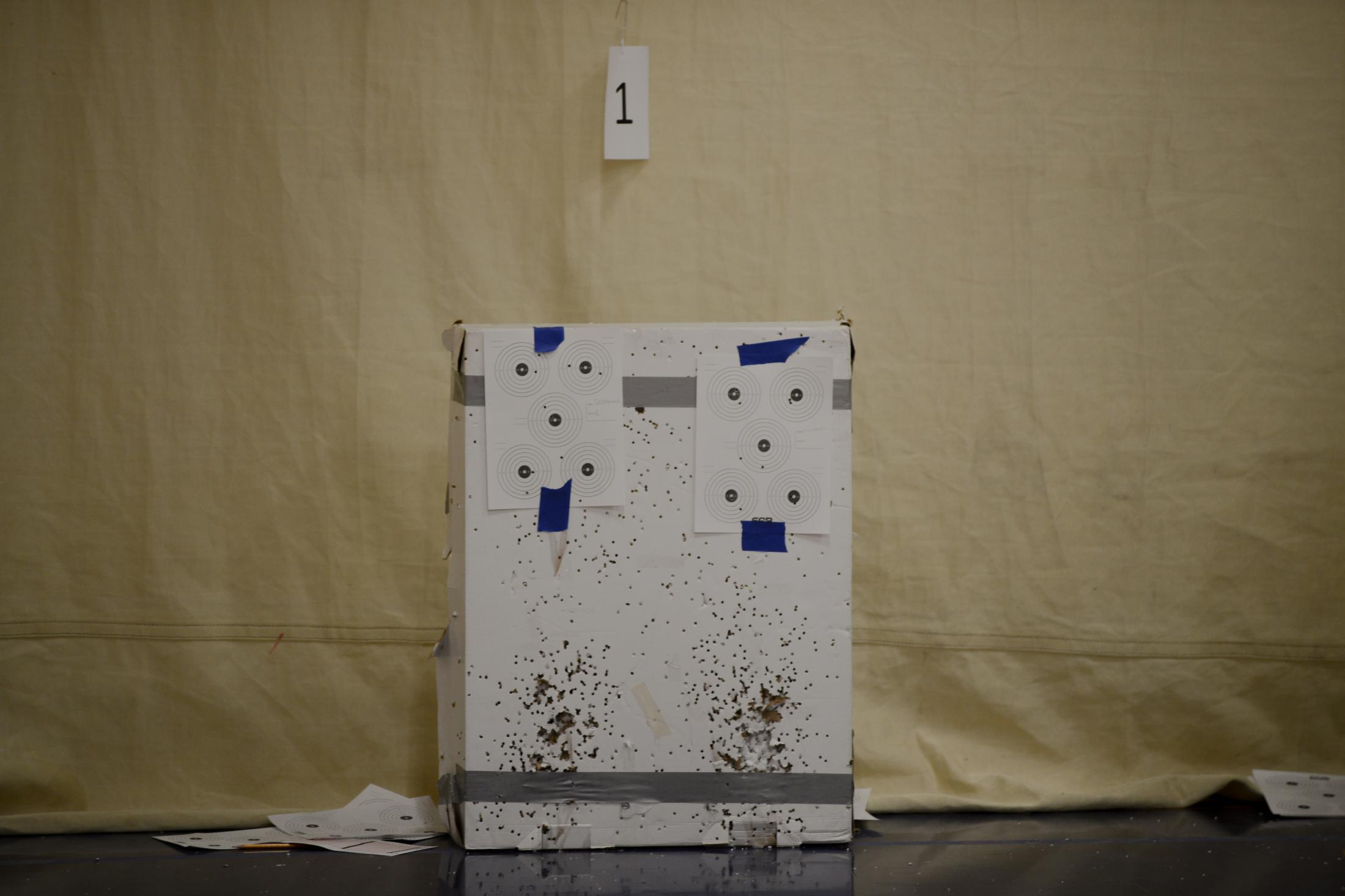A set of targets sit on cardboard filled with holes from air rifles between rounds at a Student Air Rifle Program tournament in the gym of Clever High School in Clever, Missouri on November 14, 2019. The SAR is funded in part by the NRA Foundation.