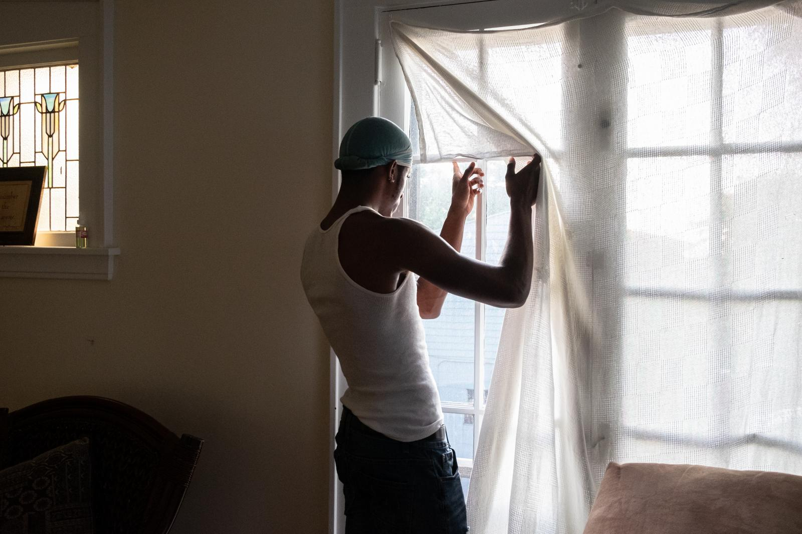 Blair Seals, 20, native of Syracuse, New York looks out the window of the apartment he shares with his brother.