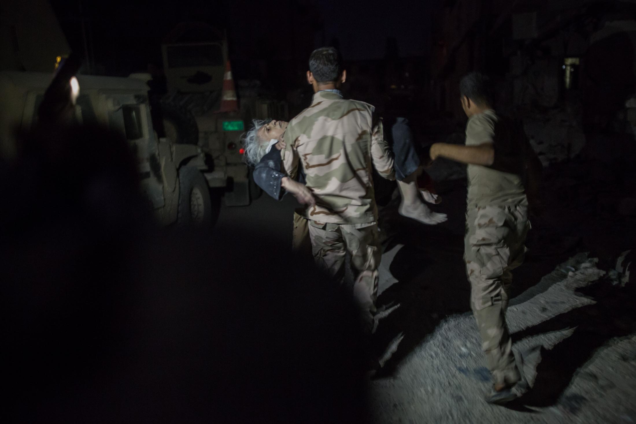 Mossul Ouest le 5 juillet 2017, Des hommes et des femmes qui fuient la vielle ville arrivent sur les positions de l'armée irakienne, en pleine nuit. Certains sont blessés et ont besoin d'aide. Un soldat porte une dame agée.