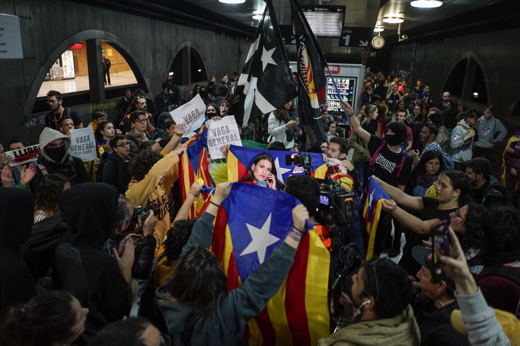 A reporter of The Spanish Television is surrounded by Esteladas or Independence flags, as demonstrators block a train rail at the subway in Barcelona, during a general strike in Catalonia, Spain, Thursday, Feb. 21, 2019. Strikers advocating for Catalonia's secession from Spain blocked major highways, train lines and roads across the northeastern region.