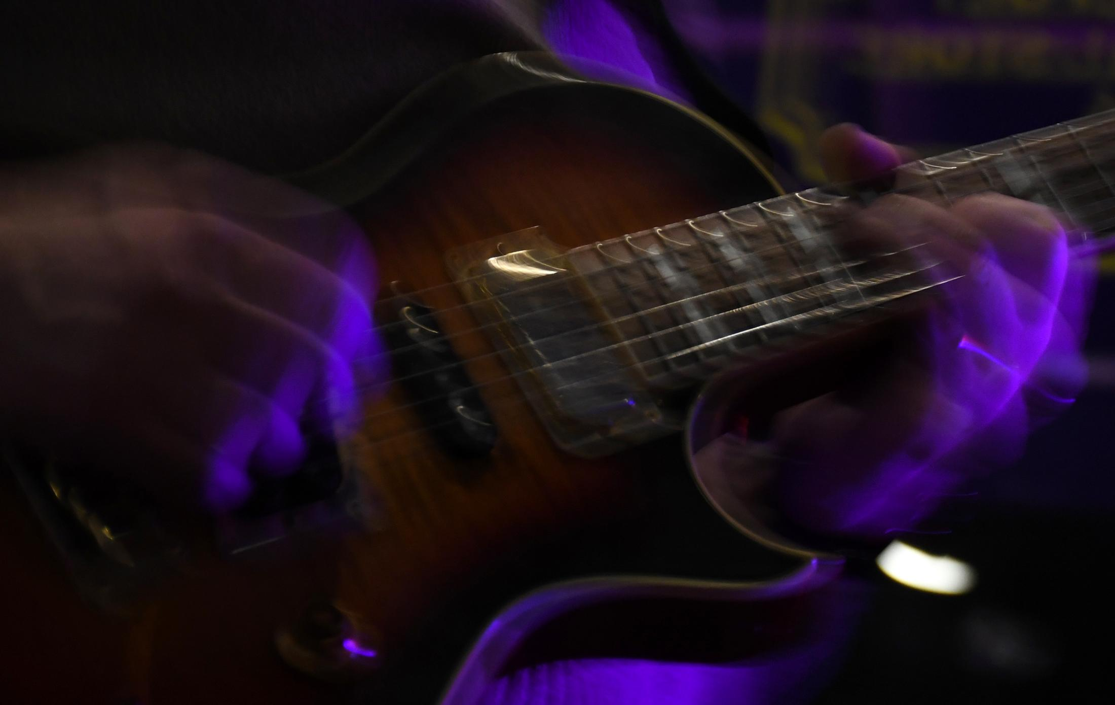 """Larsen's strings and fingers move at high speed as he plays his solo in """"Too Thick to Drink"""" at the Rocheport General Store on Friday, Nov. 15, 2019, in Rocheport, Missouri. The song receives part of their first album's name """"Too Thick to Drink, Too Thin to Plow"""" that was released on summer of 2019."""