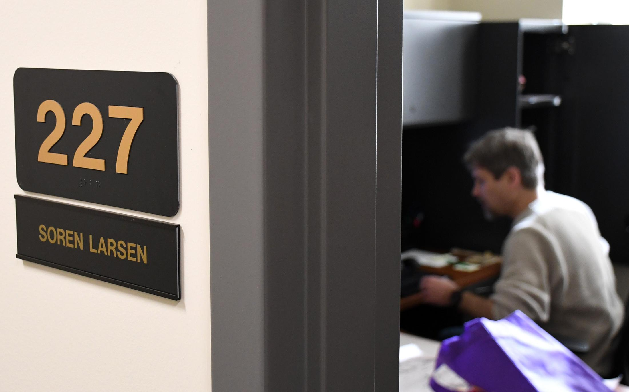 The name Soren Larsen is showed at his office door. His office is at the University of Missouri Geography Department, located at Stewart Hall. Larsen is normally busy the entire day and has to have lunch while working on future lectures and answering emails.