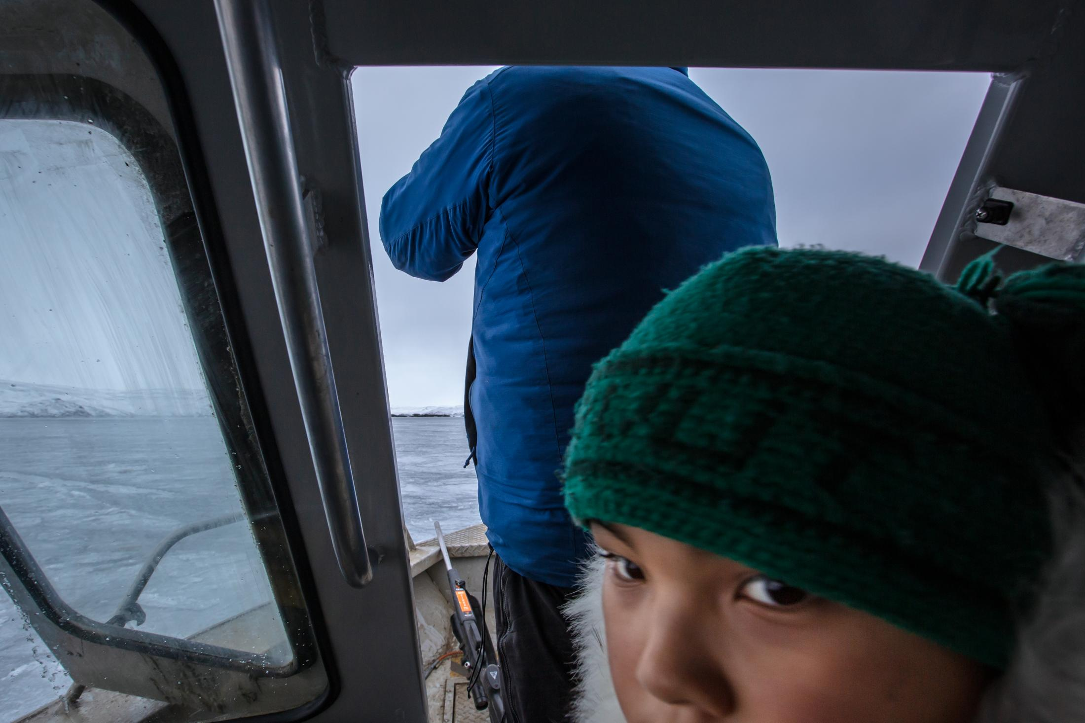After Alex Flaherty turns off the engine of the boat, Kaniq Allerton and the rest of the crew quietly scan the water for ringed seal.