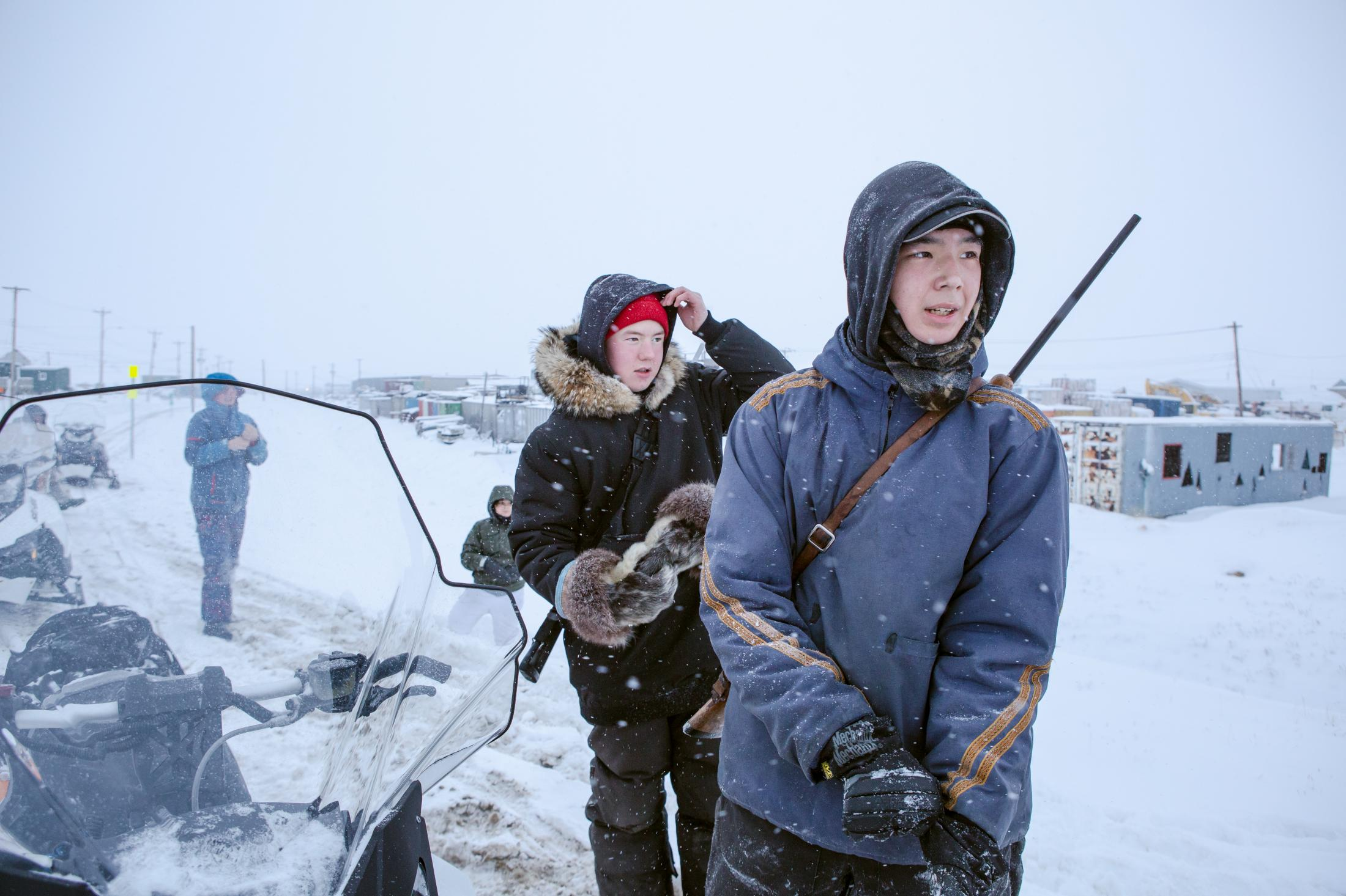 Jack Allakariallak and Simaniq Kootoo watch as older hunters recover a snowmobile from the ditch.