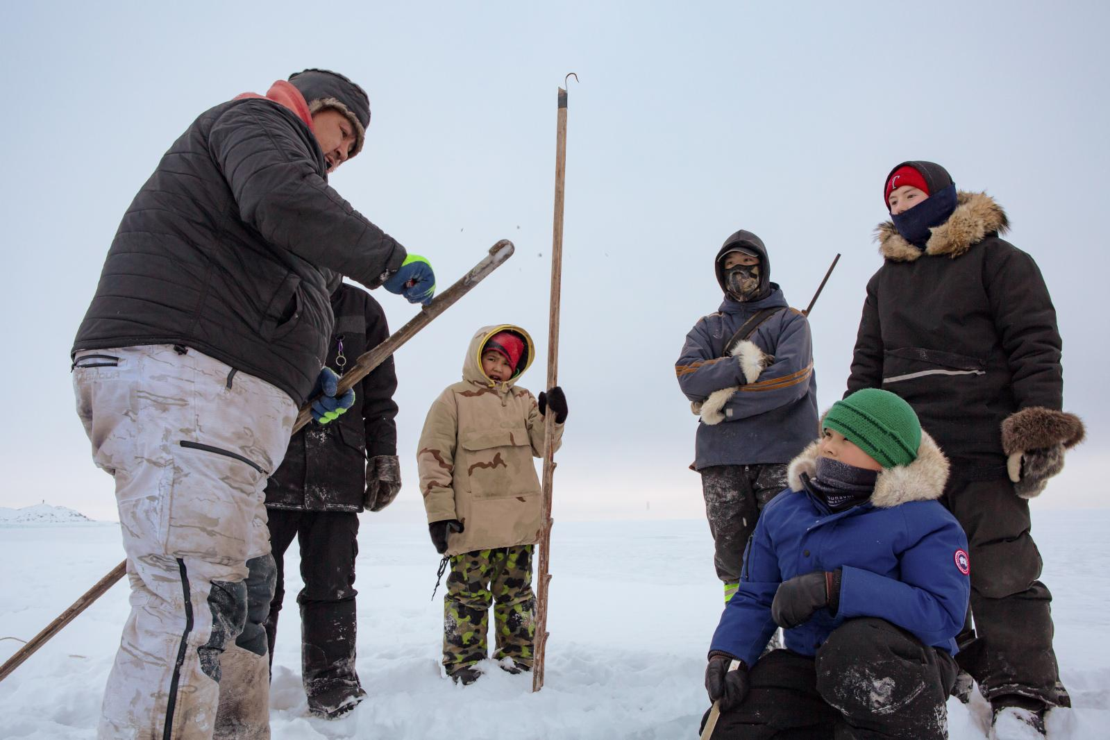 The boys watch as Kevin Kullualik demonstrates how to scrape off ice from a seal hook (niksik), which is used to pull seal out of the water.