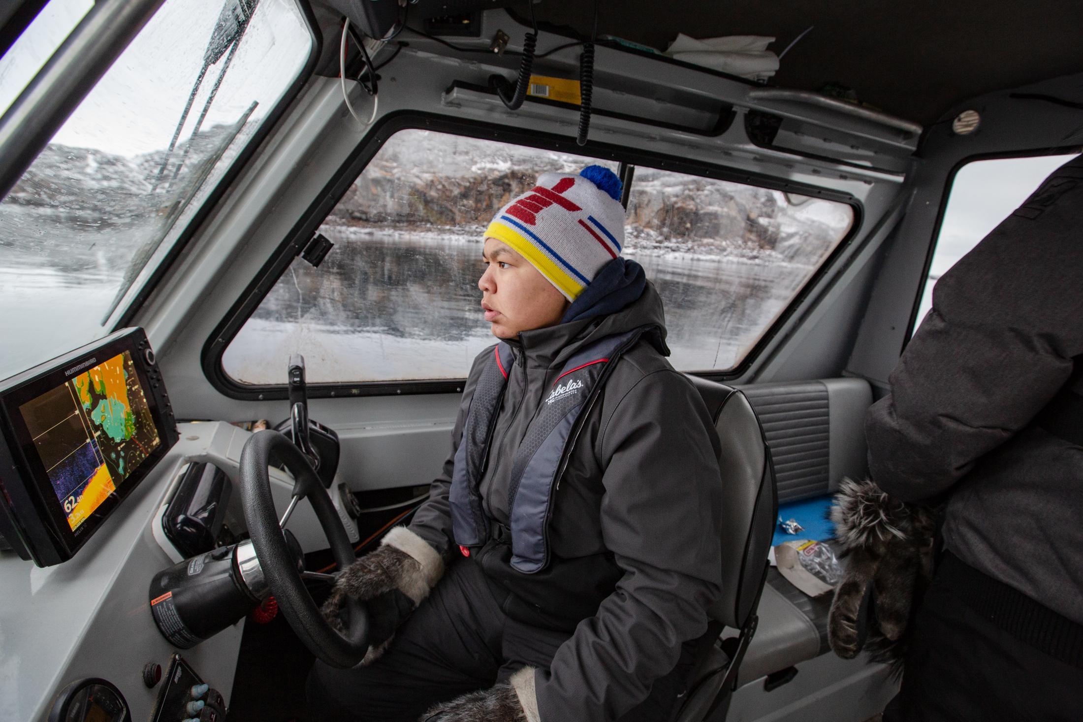 Damian Young drives the boat while Alex Flaherty is outside on the bow scanning the water for ringed seal.