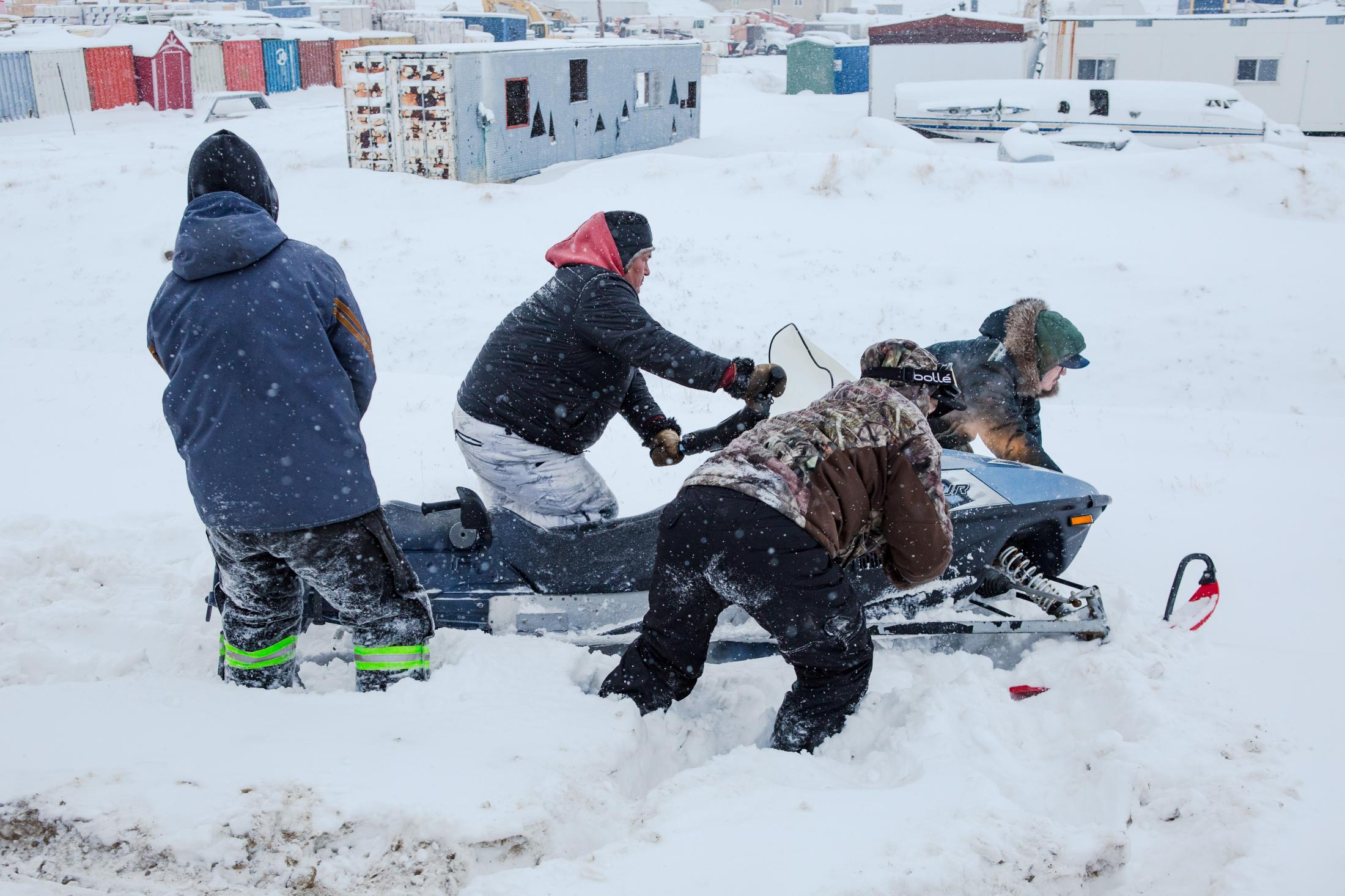 Shortly after a snow fall, the roads got icy and Simaniq veered his snowmobile into a ditch. It took a few pairs of hands to guide it out.