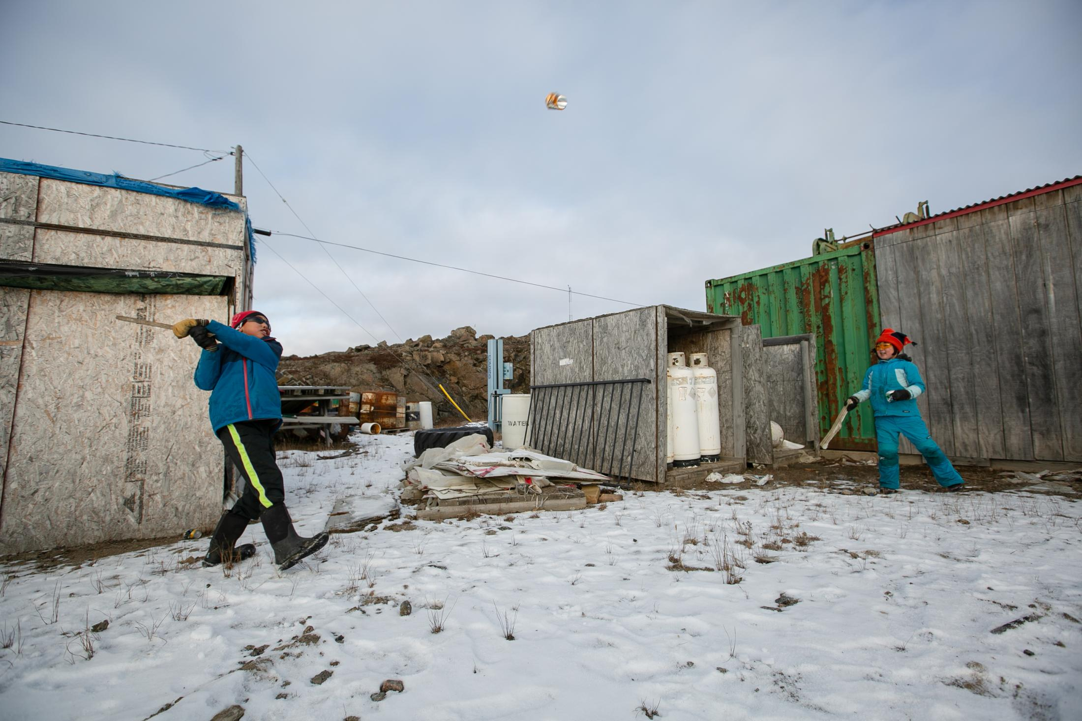 Inuki Wilman, left, and Béatrice Allerton have fun playing baseball with a pop can to pass time while Kaniq works on his hunting tools during a workshop.