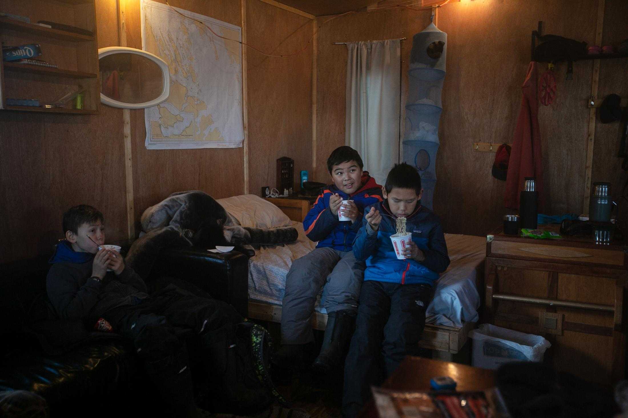 The hunting group stops for lunch at Kevin Kullualik's cabin, during which the younger boys watched The Goonies.