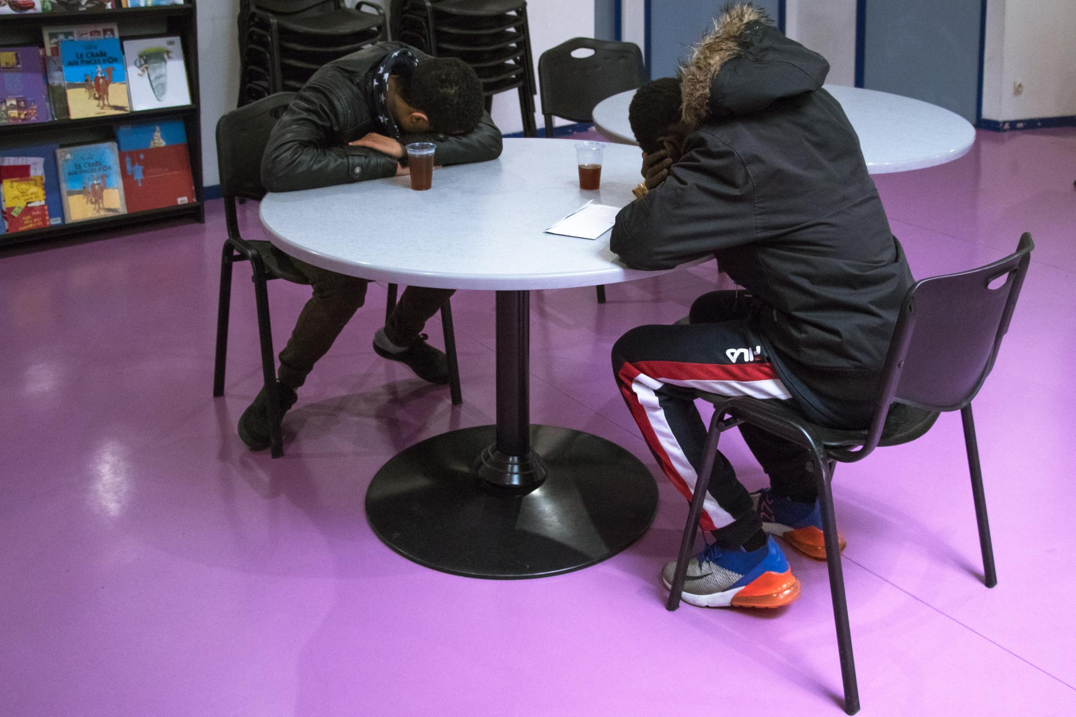 Deux jeunes exténués, un marocain (à gauche) et un malien (à droite), attendent leur entretien avec un évaluateur dans la salle d'attente du DEMIE 75 (Paris 11ème). Dramane (à droite) a dormi dans la cuisine d'un foyer.