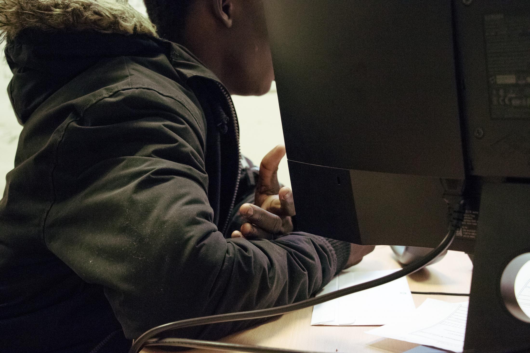 Dans le bureau, Dramane répond aux questions de l'évaluatrice. Le questionnaire, construit conjointement par la Croix Rouge et l'Aide Sociale à l'Enfance, porte sur la famille, le parcours migratoire, la scolarité, les projets. Dramane explique avoir rejoint l'Espagne depuis le Maroc par la mer. Sans parcours scolaire, il aurait quitté le Mali pour des raisons économiques.