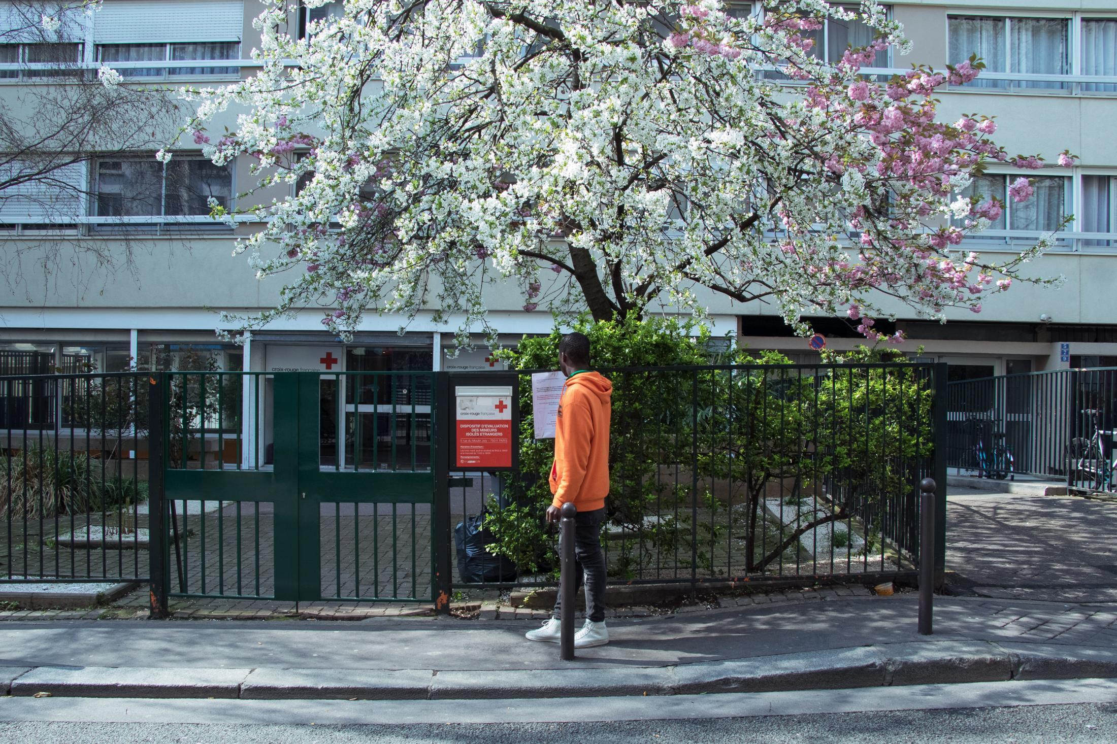Devant la grille du portail du DEMIE 75, un jeune ivoirien lit les consignes d'accueil.