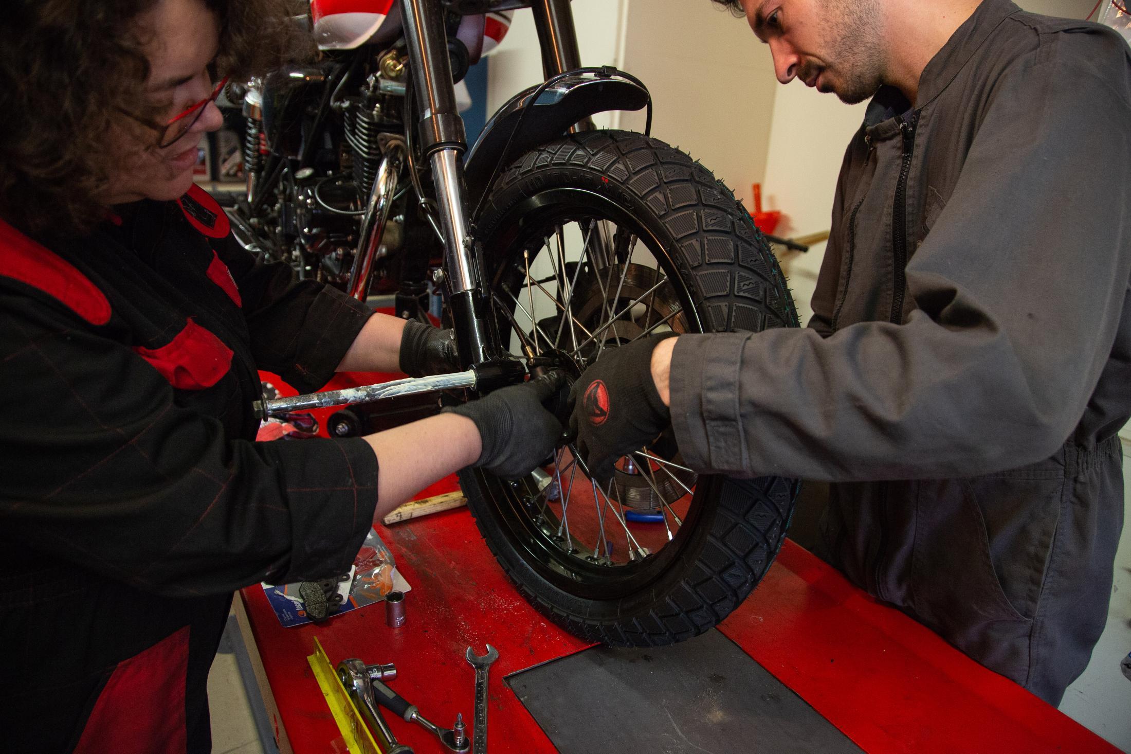 Sophie et Augustin installent ensemble la roue avant de la moto.