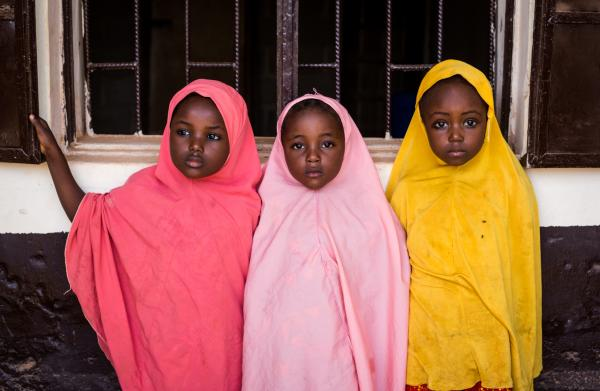 Some preschoolers stand outside as they wait for their session to begin. The pre-school safe space has 3 sessions a day and accommodates 15 girls per space.