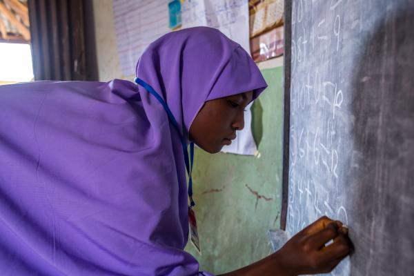 A young teen girl writes on the board during a numeracy class in the out of school safe space. The out of school safe space is for married teen girls that have never been in school. The girls are taught basic literacy and numeracy skills.