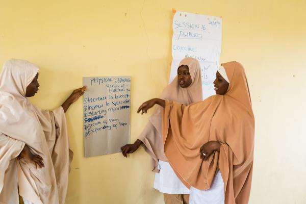 Some teen girls present their work to their peers as part of their class activity during a session in the out of school sees space.