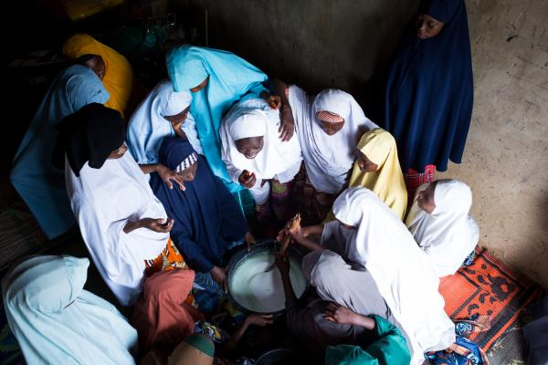 Teen girls gather to learn how to to make liquid soap during a vocational training.