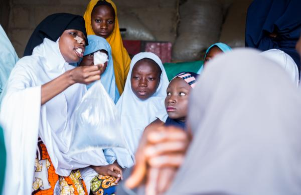 A young teacher (white hijab) shows the teen girls the ingredients for soap making during a vocational training. In February 2019, the Centre for Girls Education set up a safe space dedicated to vocational training for young teen girls.
