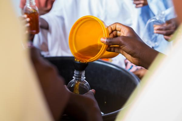 A young teen girl dispenses disinfectant into a plastic container shortly after it was made. The teen girls who partake in the vocational training, learn how to make household items that can be sold for profit in their community.