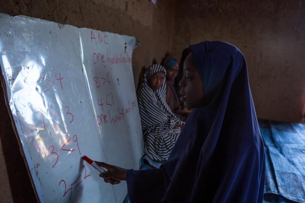 A young girl writes on the board during a numeracy class in the out of school safe space in Marwa community, Zaria.