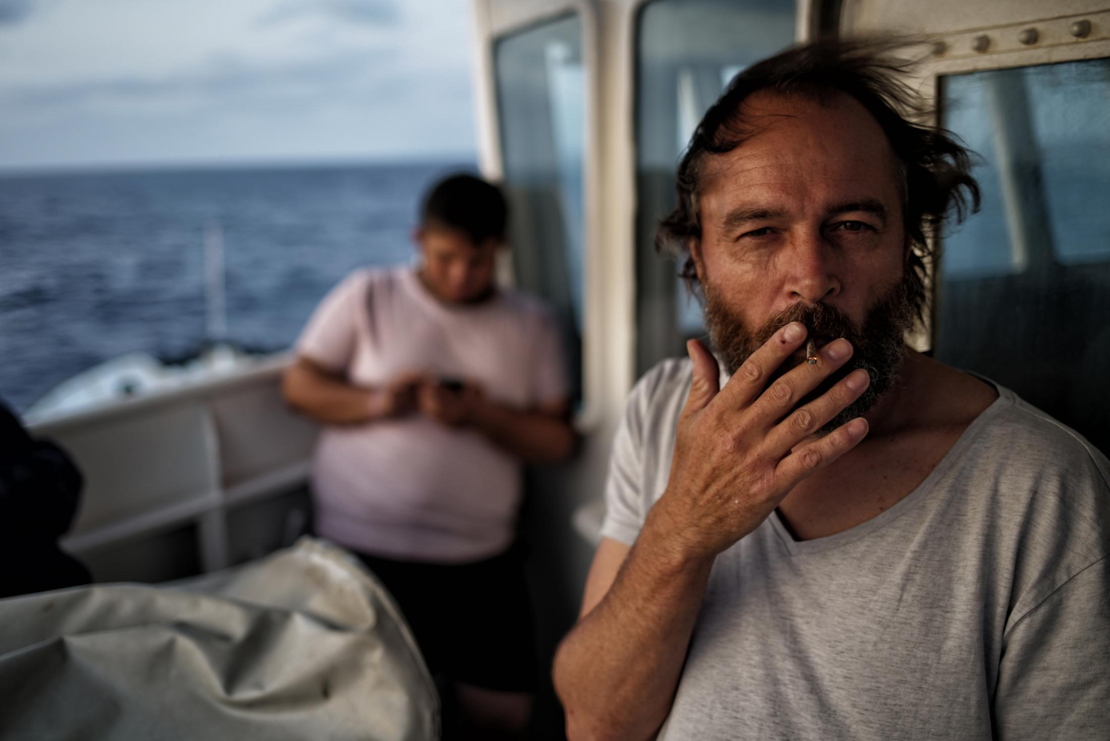 A crew member onboard the 'Aquarius' vessel smokes a cigarette outside on the deck while waiting for a rescue at sea on Monday June 20, 2016. The medical aid group Medecins Sans Frontieres (MSF) and the rescue group SOS Mediterranee cooperate on the vessel to rescue migrants on their way from North Africa to Europe. (AP Photo/Bram Janssen)