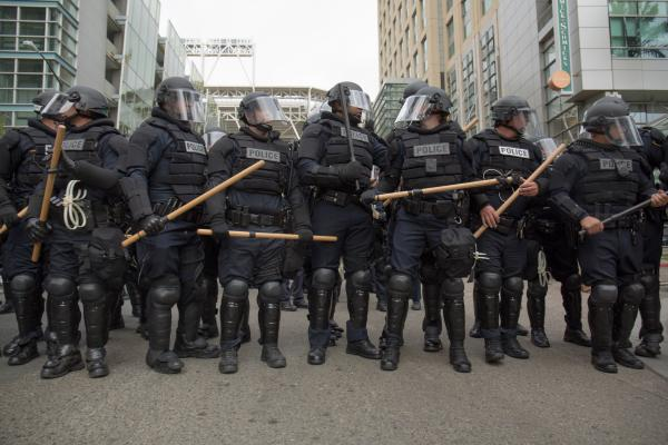 Police in riot gear hold batons outside of the San Diego Convention Center as Donald Trump supporters and protesters began fighting each other after a campaign rally on May 27, 2016.
