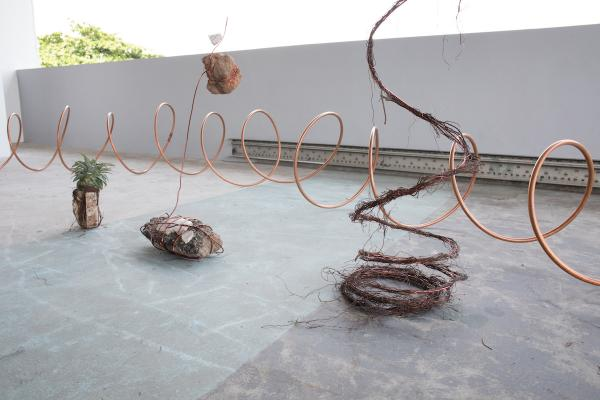 "Installation views of A Walk Sculpture, Lagos, 2019. Produced after 6 days of walking for the Lagos biennial in October 2019.  The hollow copper spirals that circulate through the structure of the installation are parts made for Air Conditioning units and with an essential function to move cool air through its coils. The spirals are also a three-dimensional take on my drawings called ""Walk Maps"" that I usually draw on walls and paper. Copper is a symbolic material used here to represent a circulatory system that connects and moves"