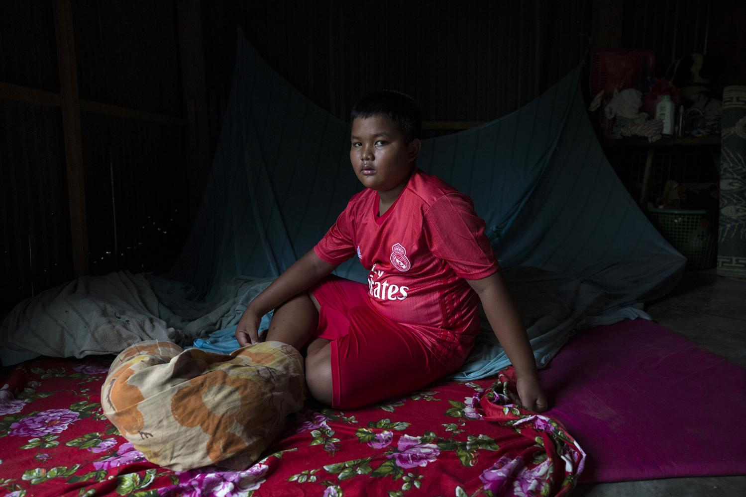 Chan Pheakdey, 10, sits in the doorway of his house after he was released from the Angkor Hospital for Children earlier that day. During the rainy season a constant presence of water makes perfect conditions for mosquitos with his sister, mother and neighbours all getting sick from dengue fever this year. Siem Reap, Cambodia - October 2019