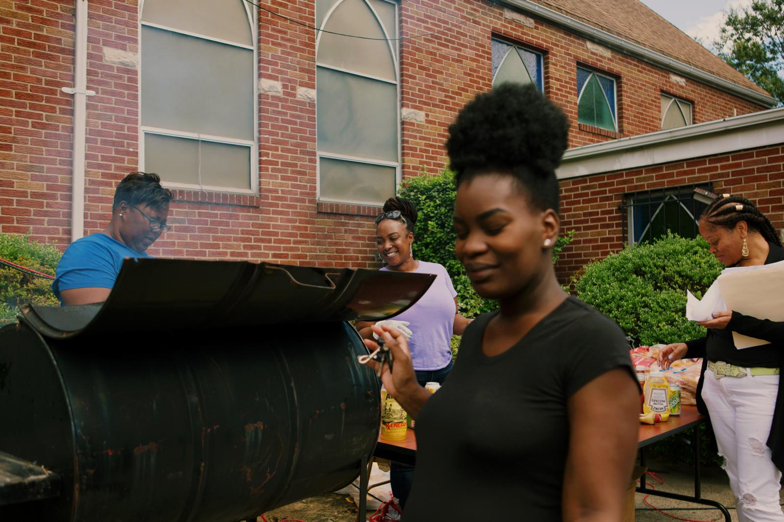 Joy Ligon and Nicole Holloway serve hotdogs and hamburgers to the attendees at the block party hosted by The Shiloh Baptist Church of Jamaica in Queens, New York.
