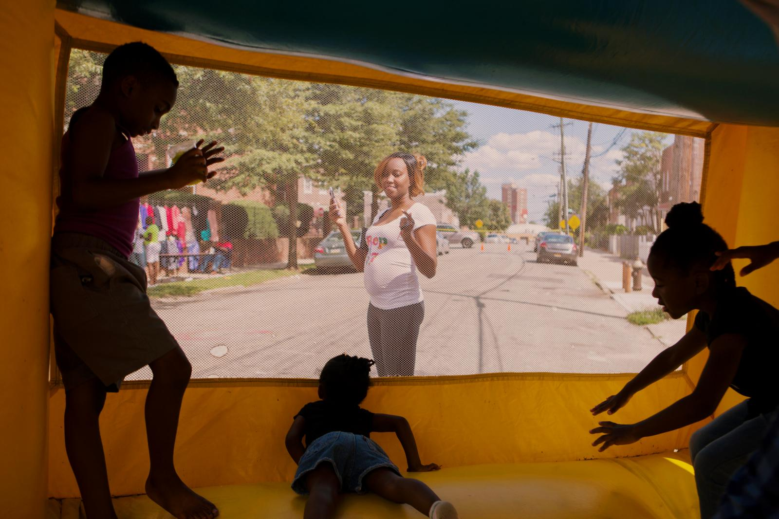 Tiffany Moreau looks out for her kid playing inside the inflatable bounce house at the block party hosted by The Shiloh Baptist Church of Jamaica in Queens, New York. Moreau mentions that she loves to see the community gather together.