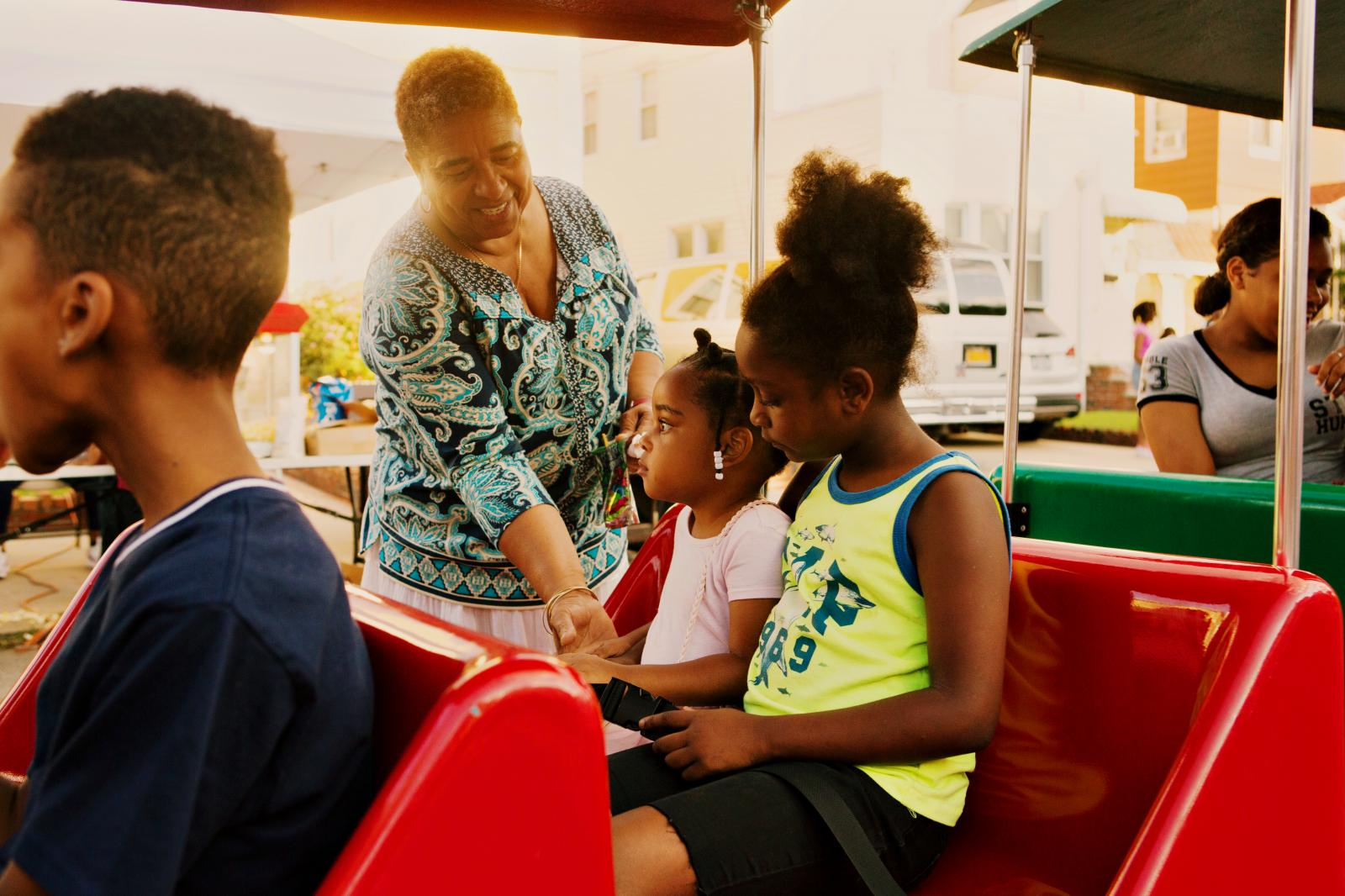 Cislyn Ricketts helps her granddaughter McKenzie Robinson, 3, get on a ride on the trackless train from OnTimeEntertainment during the block party in Laurelton neighborhood in Queens, New York hosted by Sudan Deane.