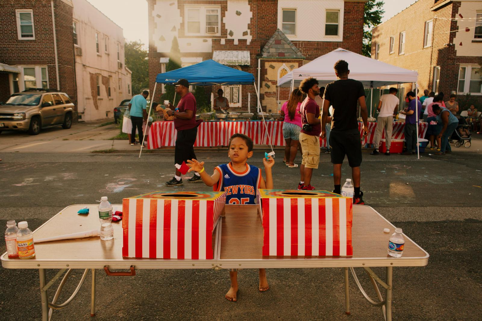 Isaac Walters, 5, plays Cornhole at the block party hosted by The Shiloh Baptist Church of Jamaica in Queens, New York.