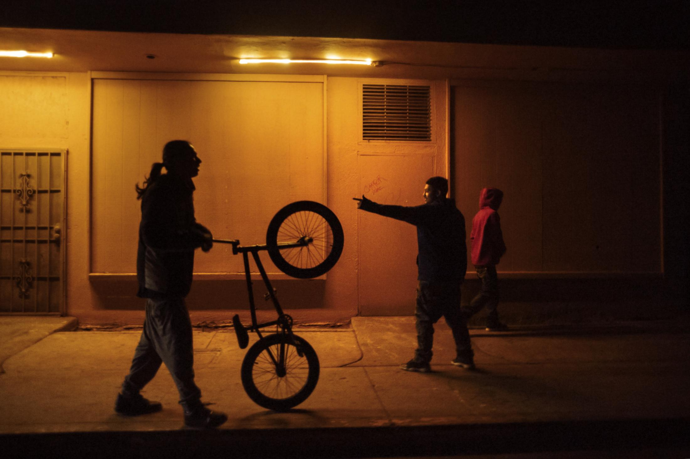 TRG (Tiny Rascal Gang) gang members quickly leave an area as one of their members is questioned by a MAGEC (gang unit) police officer in Fresno.