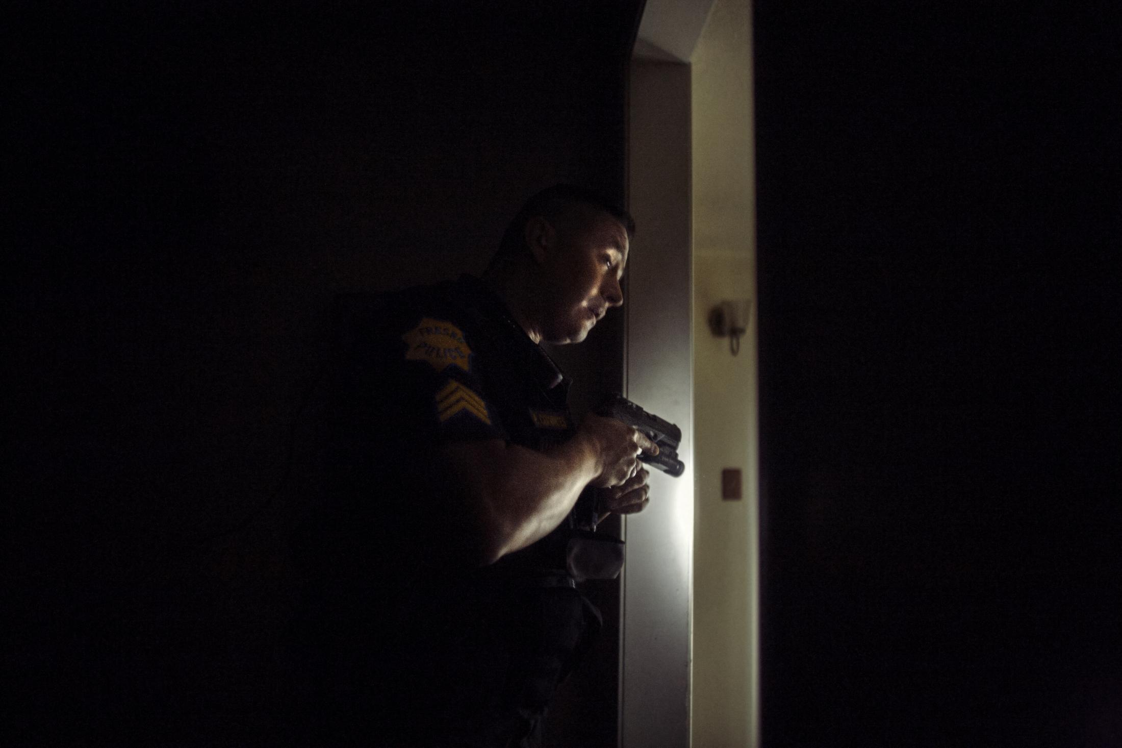 Fresno Police Sergeant Paul Cervantes of the Multi Agency Gang Enforcement Consortium (MAGEC) conducts a security sweep of a home in Fresno, CA. Cervantes was later charged with corruption and removed as head of the task force in a scandal that would lead to a shakeup of the Fresno Police department.