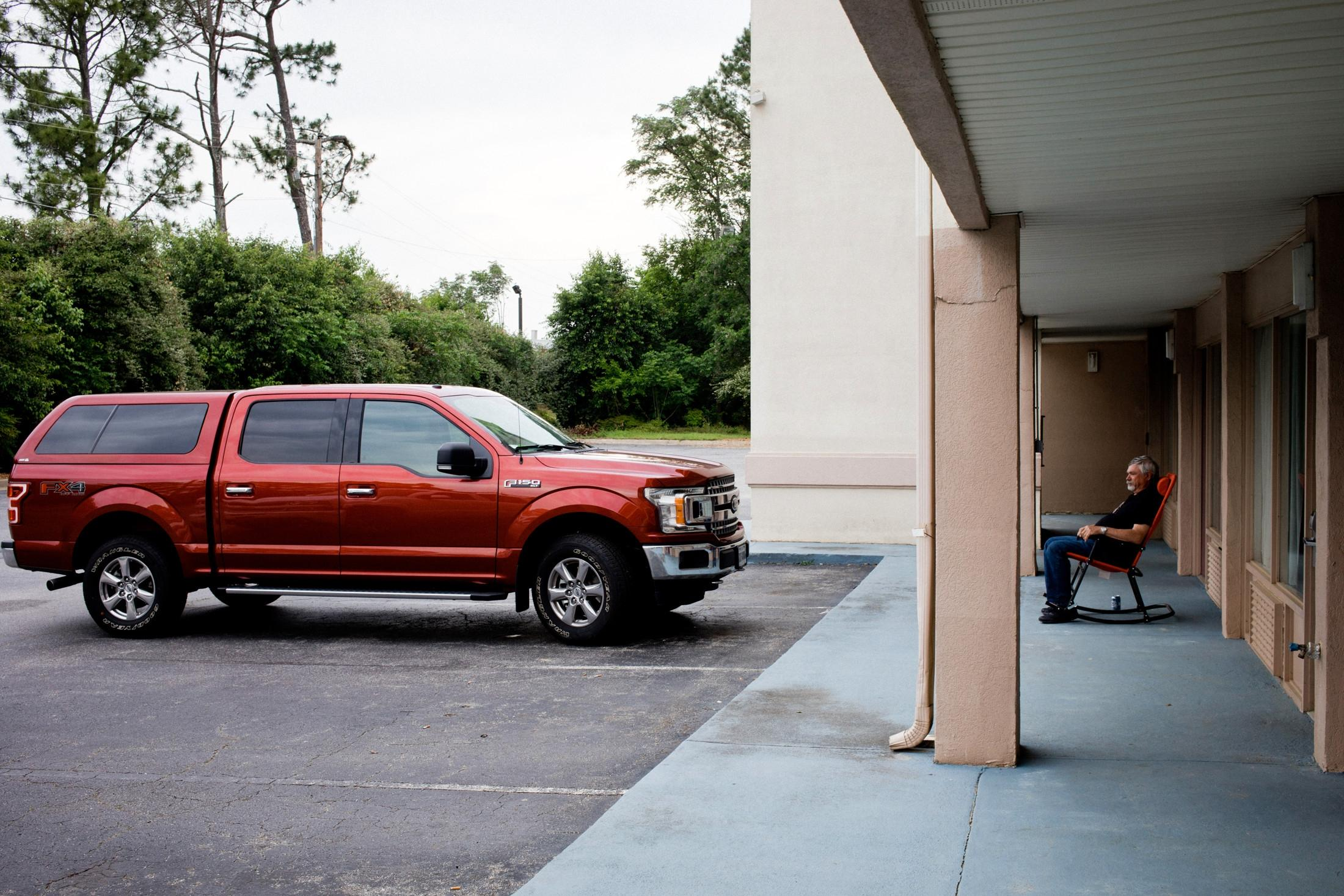 Owner of a Ford F150 resting between his car and the door to his motel room. Madison, Georgia. Image part of Automobile America project in progress.