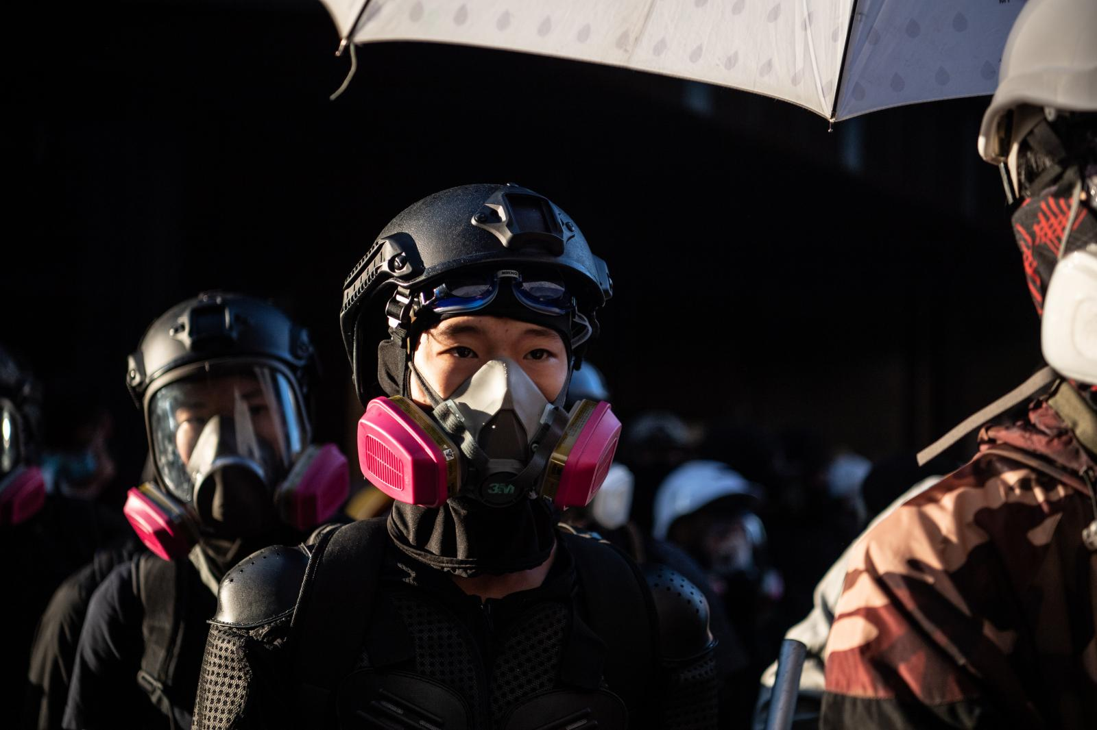 "HONG KONG, CHINA - NOVEMBER 18: Anti-government protesters stand during a lull in the middle of clashes with police at Hong Kong Polytechnic University on November 18, 2019 in Hong Kong, China. Anti-government protesters organized a general strike since Monday as demonstrations in Hong Kong stretched into its sixth month with demands for an independent inquiry into police brutality, the retraction of the word ""riot"" to describe the rallies, and genuine universal suffrage. (Photo by Laurel Chor/Getty Images)"