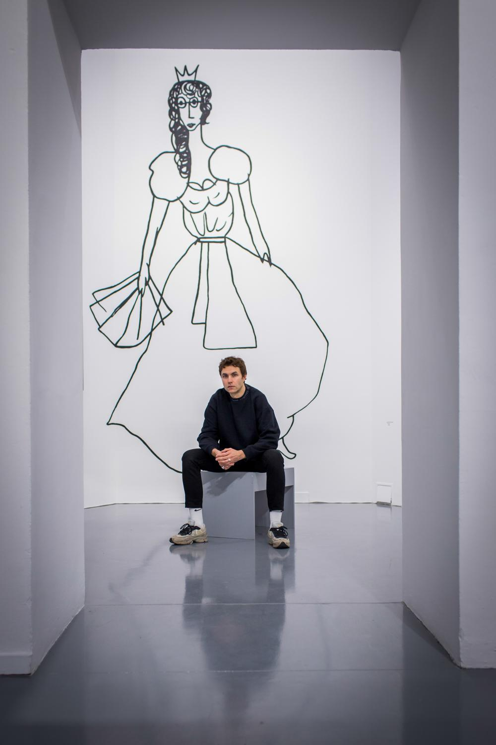 """Karol Radziszewski in front of a self-portait from his series """"1989,"""" in which the artist depicts himself as Cinderella, at the Ujazdowski Castle Center for Contemporary Art in Warsaw, Poland. A new director wants to reshape a leading Warsaw art space to show conservative works and challenge left-wing positions. Portrait for The New York Times"""