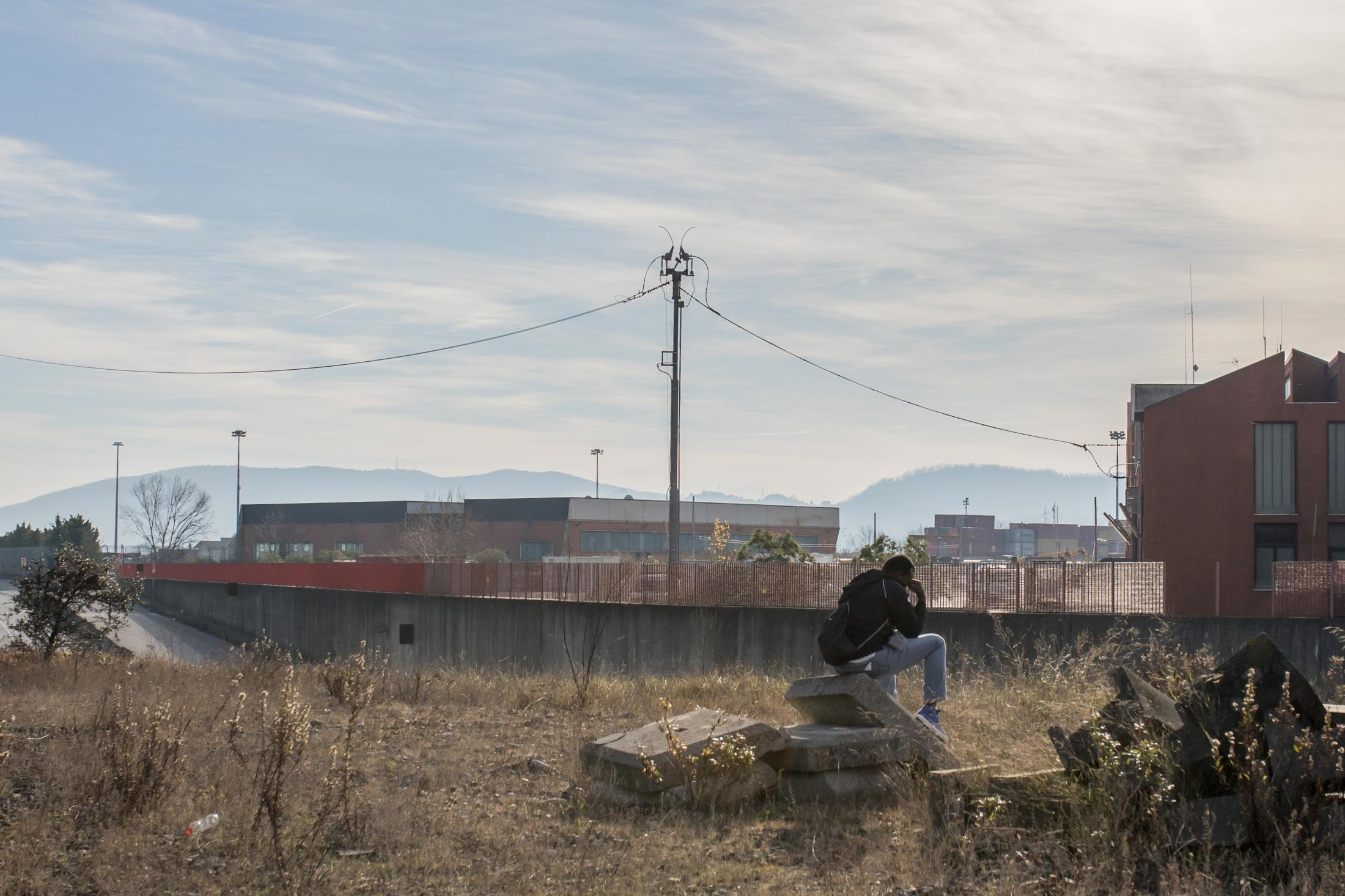 L oneliness and discouragement of a migrant beside the railway line (Italy)