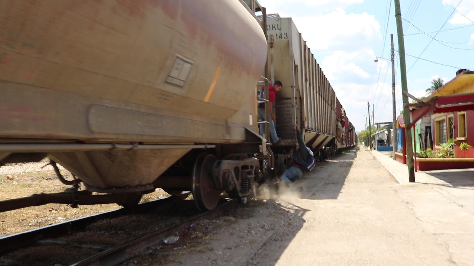 While trying to board the moving train called la Bestia (the beast), a migrant loses his balance in Tenosique (Mexico)