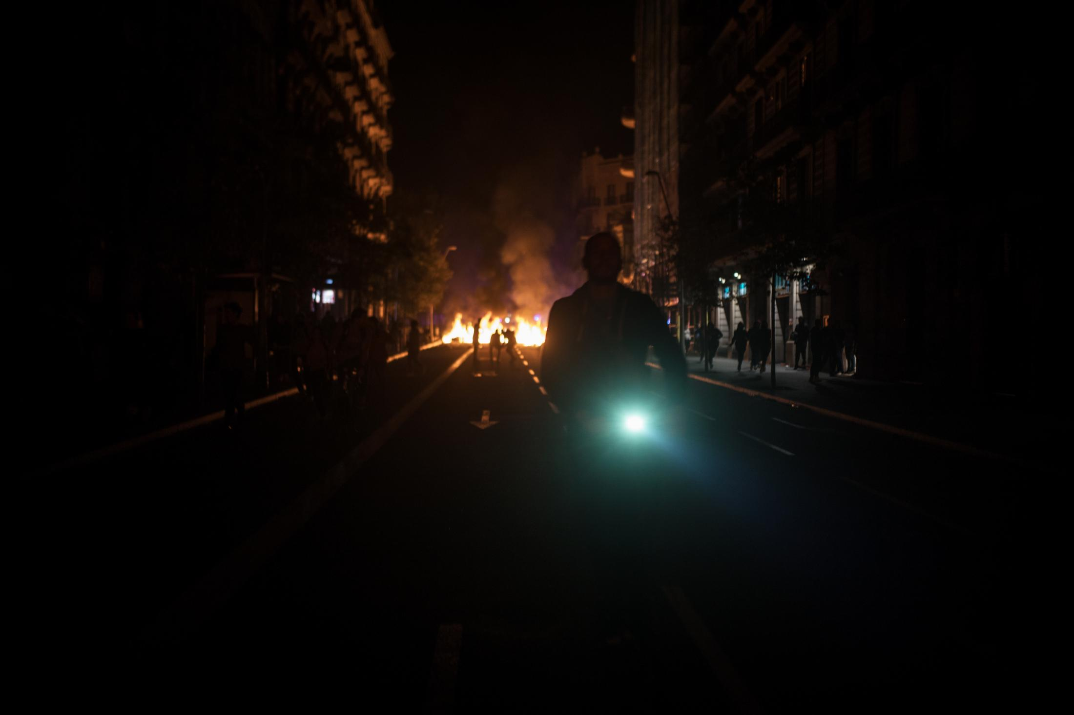 """October 18, 2019. Barcelona, Spain. A man rides his bicycle towards roads with fire barriers. The movement driven by """"frustration"""" as a result of the """"repression"""" experienced asks Spain to sit and talk to solve the problem and claims the value of the words """"resistance"""", """"unity"""", """"referendum"""", """"democracy"""", """"rights"""" and """"justice"""" while reborn with the will to generate hope and fighting fear. Many Catalans believe in a new generation of activists who feel gagged and takes the street while the protests and the political paralysis of Spain leave the sensation of a dead-end. Catalonia has been counting the political cost after protests swept across the region. Hoteliers, restaurants, and shops say takings fell up to 50% after the violence, and future bookings may be hit. The tourism association, Barcelona Oberta, estimates that economic activity in the city center – from shops, hotels, and restaurants – fell by between 30% and 50% in the week after the leaders were sentenced, either because fearful customers stayed away or businesses closed to avoid being looted."""