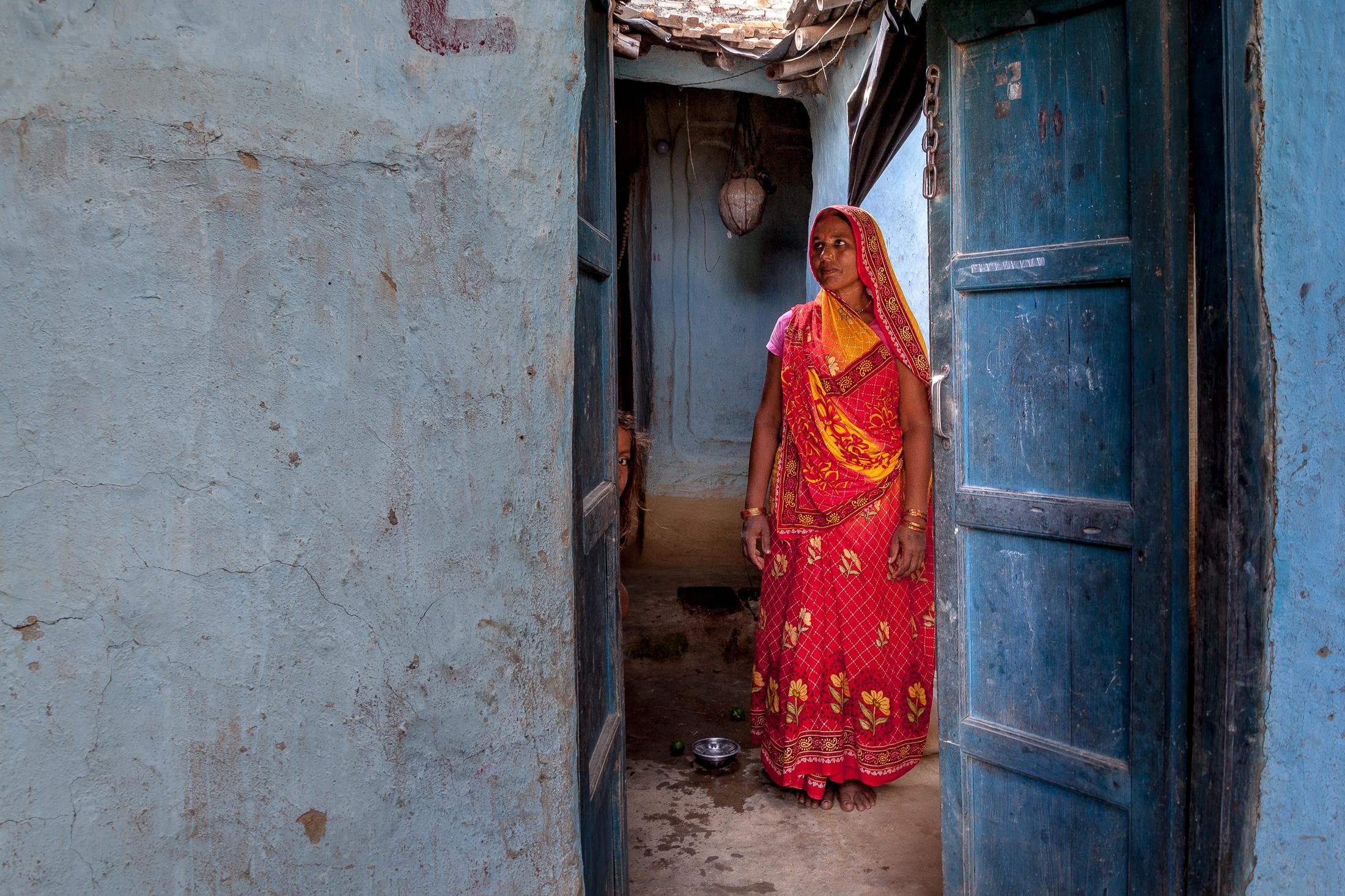JANAKPUR, NEPAL - JULY 23: Bobita Devi Mahara, 42 years of age, is seen through the door of her home in a remote village on July 23, 2015 near Janakpur, Nepal. Bobita is a Maithil woman who has started to break the Maithil tradition which often keeps women inside their homes and forces them to hide their faces while speaking to other people. Bobita is working as a road construction worker since 2014, earning income to help her family, and especially to send her daughter to school. Photo: © Omar Havana
