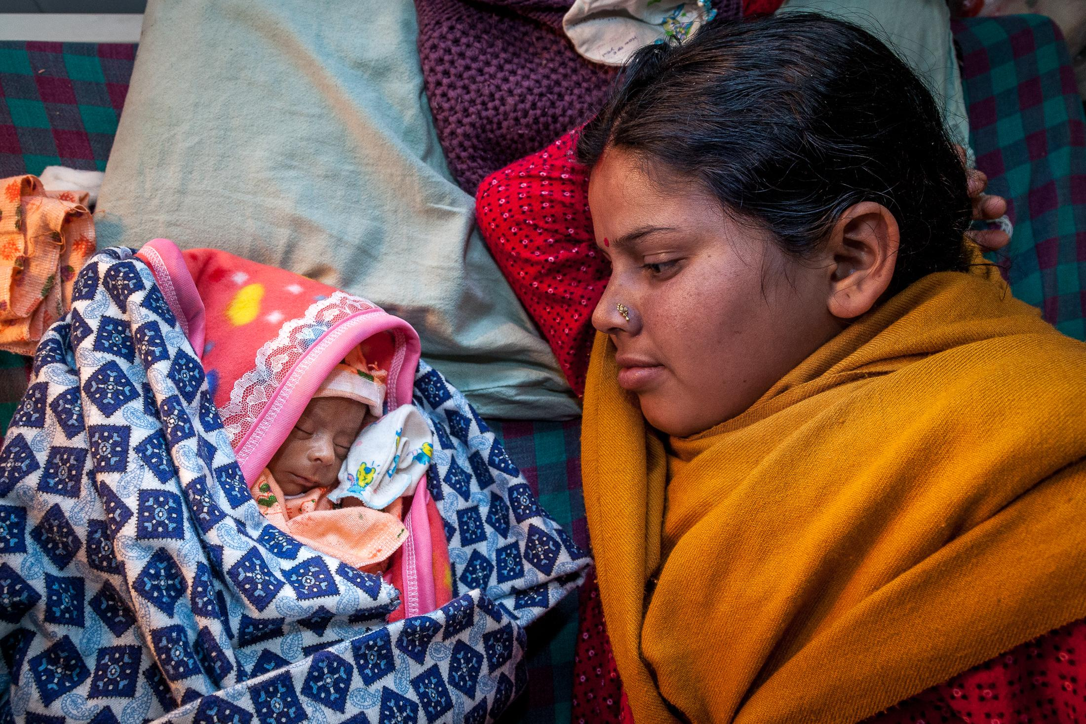 KATHMANDU, NEPAL - FEBRUARY 12: Munni, 18 years old, lays in a bed with her 21-days-old baby who was born prematurely at 28 weeks at the T.U. Teaching Hospital on February 12, 2015 in Kathmandu, Nepal. Premature babies are particularly at risk of health complications, including breathing, heart, brain, temperature control, gastrointestinal, blood, metabolism and immune system problems. From 1996 to 2006, Nepal reduced by close to 50% its maternal mortality rate, going from 539 deaths in 100,000 to 281, making Nepal a success story. However, each year, 57,000 under-five children still lose their lives, with 54% of those cases occurring within the first month after birth. In 2013, only 50% of births were attended by skilled birth attendants. Several issues remain to be addressed with regards to maternal and newborn health, including tackling inequalities, improving access to care in remote areas, improving quality of care, increasing the use of family planning methods, and reducing malnutrition. Photo: © Omar Havana for UNICEF