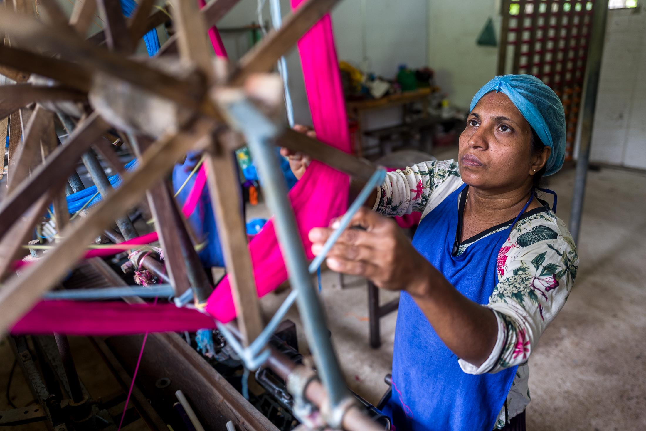 WELGALA, SRI LANKA – DECEMBER 13: A female worker performs her duties inside one of the handloom wards at the Selyn factory on December 13, 2018 in Welgala, Sri Lanka. All workers at the Selyn factory come to work from nearby villages. Most workers arrive early in the morning to the factory riding bicycles that the company helps them to buy by paying half of the price. Workers work daily 9-hours shifts, including a 1-hour lunch break. Photo: © Omar Havana for  IFC