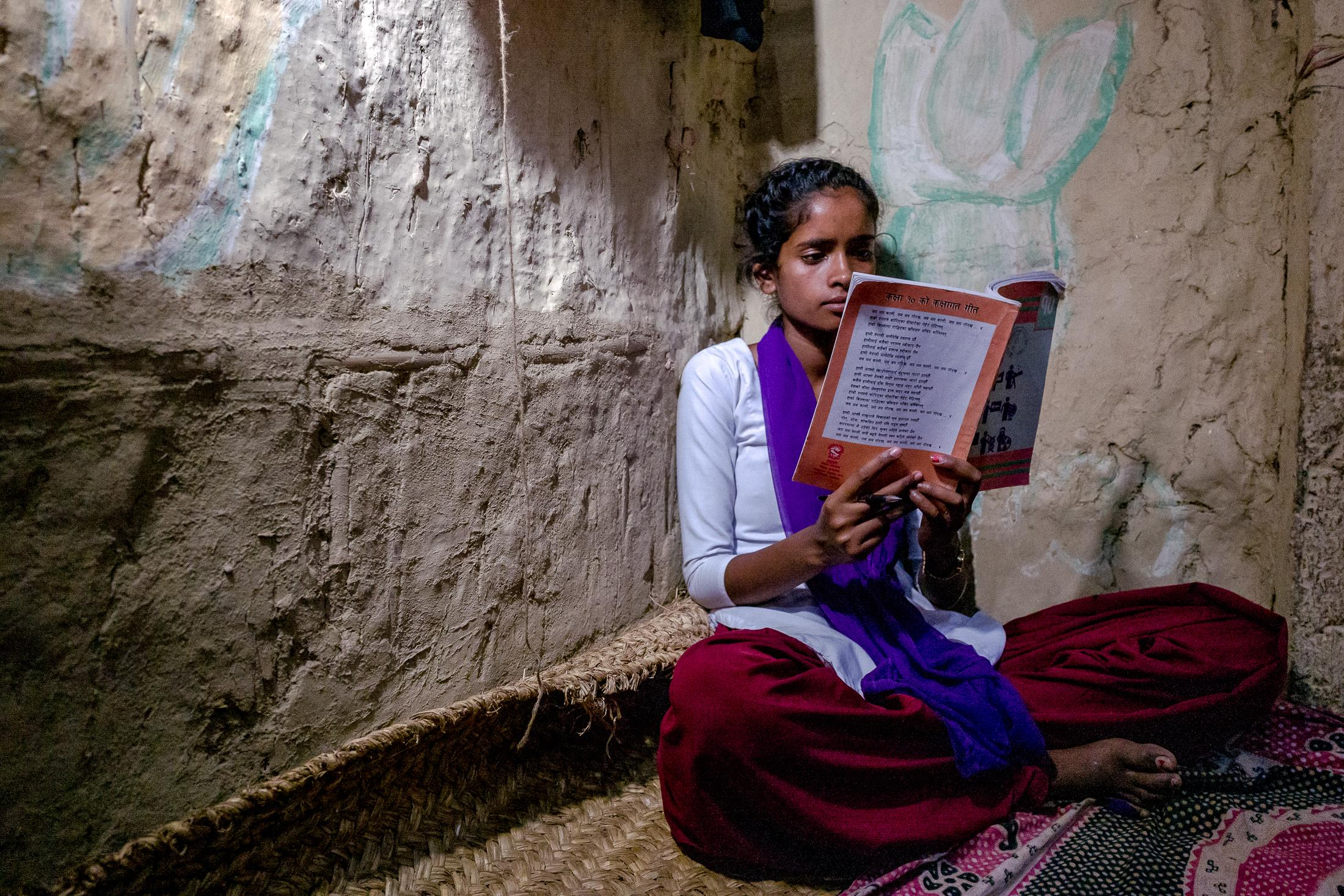 "DOBINI, NEPAL - MAY 29: 15-years-old ""Little Sister"" Arti reads a book sitting in a corner of her bedroom inside her home on May 29, 2019 in Dobini, Nepal. Arti was only 14 when her parents arranged her marriage. Big Sister, Anu, stepped in. Working with her parents and the community to delay marriage and keep Arti in school. Arti is now focussing on her studies, with the hopes of becoming a teacher. Photo: © Omar Havana for VSO International"