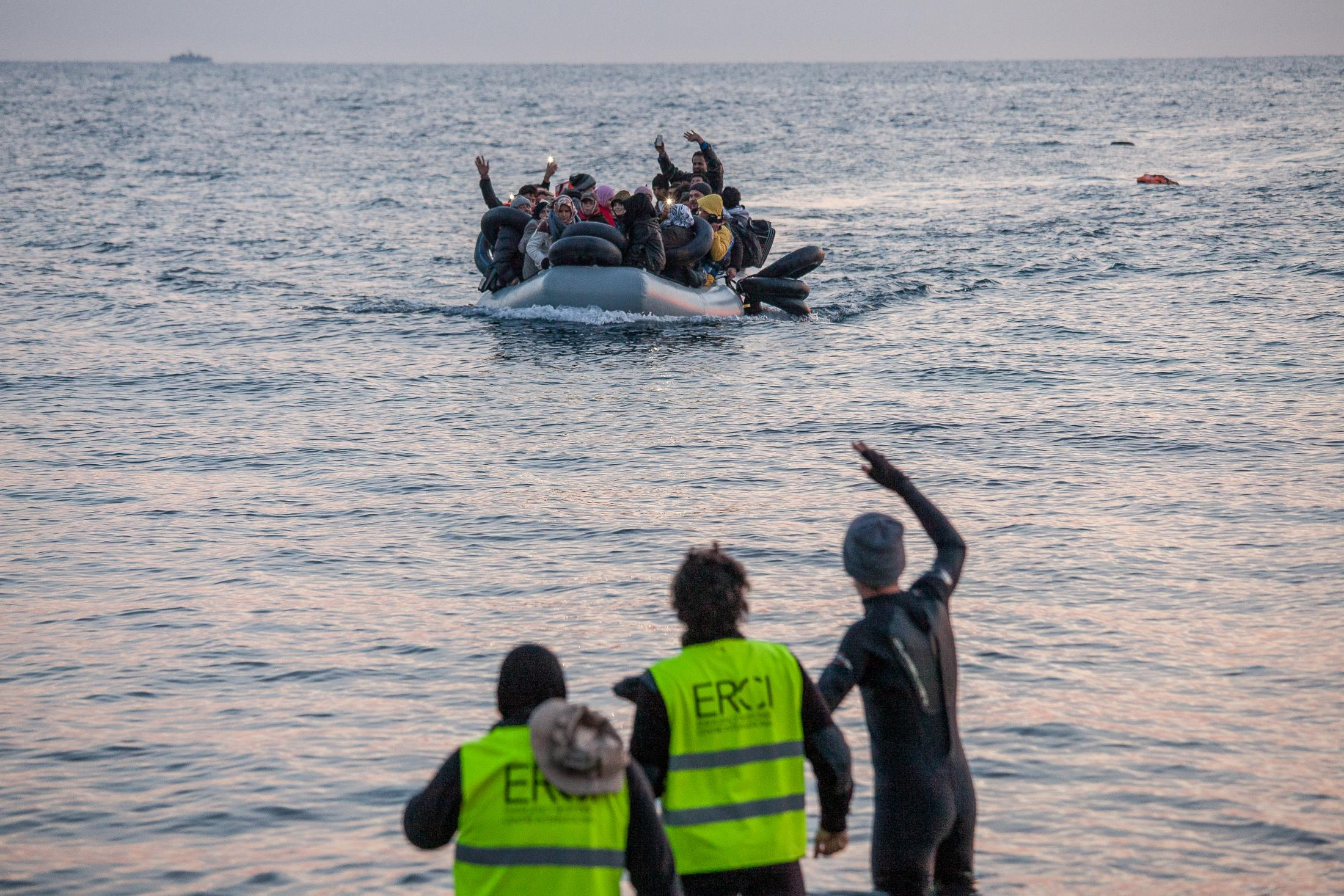 MYTILINI, GREECE - FEBRUARY 09: Volunteers guide refugees to a safe zone arriving at Katia beach in a dinghy during the early morning on February 09, 2015 in Mytilini, Greece. Dozens of volunteers watch day and night on the beaches of Lesvos for the arrival of refugees. Volunteers are the firsts to help refugees that are not rescued by coastguards that watch the Aegean sea. Teams of doctors from different countries work together with international rescue teams in providing assistance to the hundreds of refugees arriving at the beaches of Lesvos, guiding dinghies to safe arrival areas, providing hot drinks and food, shoes, clothes and medical assistance to those arriving sick. Hypothermia is a common symptom on the refugees arriving at Lesvos after crossing the Aegean sea for more than 2 hours from the Turkish coast, from where they are smuggled into Europe. Photo: © Omar Havana for Action Aid Greece